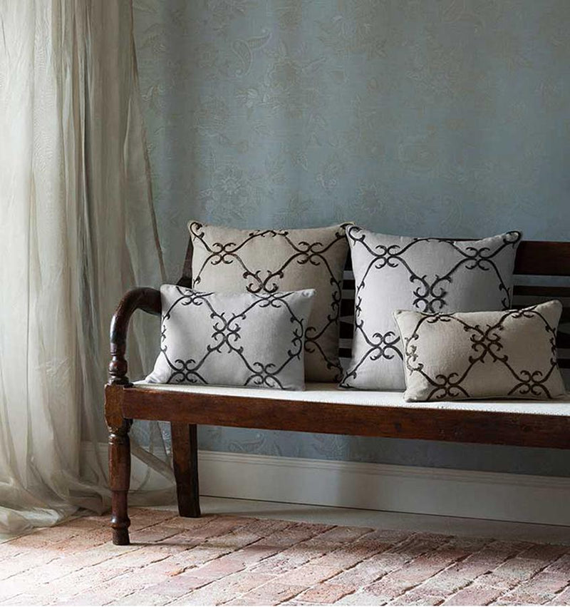 Solari pillows bear a lovely geometric scroll motif, meticulously hand-stitched with elegant beadwork in shimmery shades of dark platinum and copper.