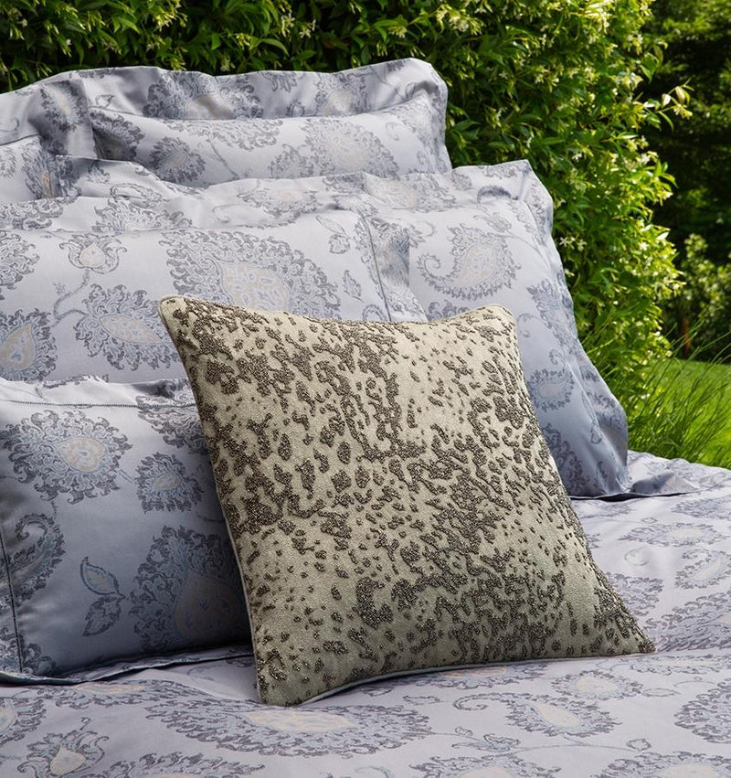 An elaborate beaded pattern is hand-stitched across the face of the SFERRA Tobiano pillow in shades of gunmetal metallic colors.