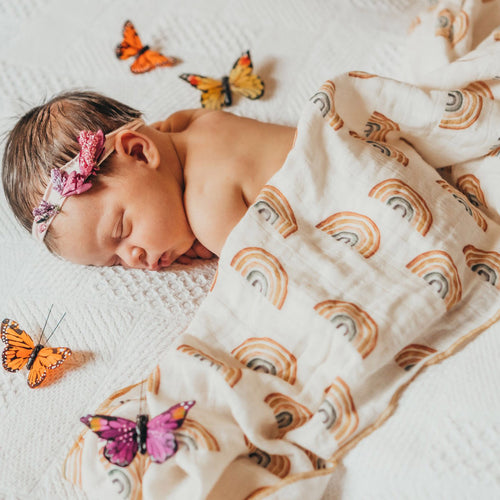 Baby covered with rainbow patterned muslin blanket
