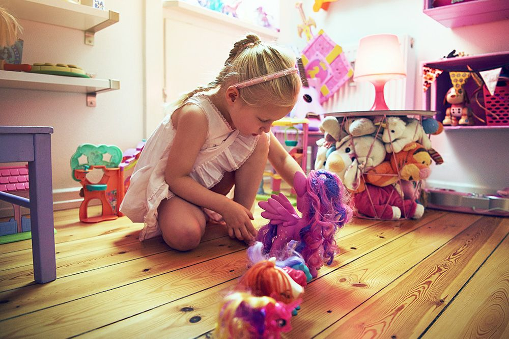 A little girl plays with toys in her room