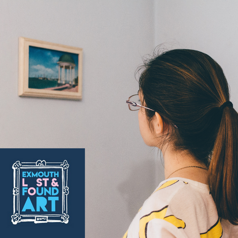 a dark haired girl looks at a small painting on a white wall