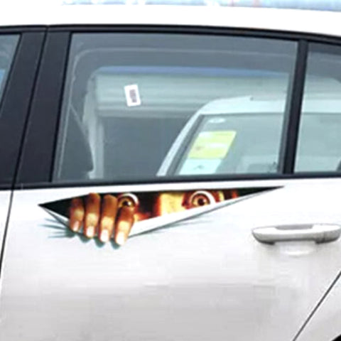 Image of Closer view of small car with auto decal that gives the illusion of someone ripping through the outside of the car and peering out from within.