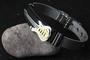 Picture of a men's guitar cuff bracelet partly displayed on top of a rock.