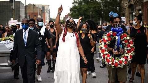 Dannielle Brown, center, marching in mock funeral on Day 34 of her hunger strike. Taken from Google Images