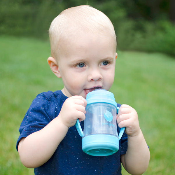 A toddler boy with a blue shirt holding a blue cup that the Glass Insert for Sip and Straw Cup.