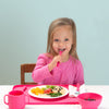 A young girl eating with matching pink dishes and utensils along with a pink Feeding Bowl made from Silicone with raisins inside.