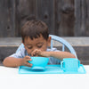 A young boy eating out of an Aqua Feeding Bowl made from Silicone with a matching aqua cup and platemat in a backyard with a wooden fence behind him.