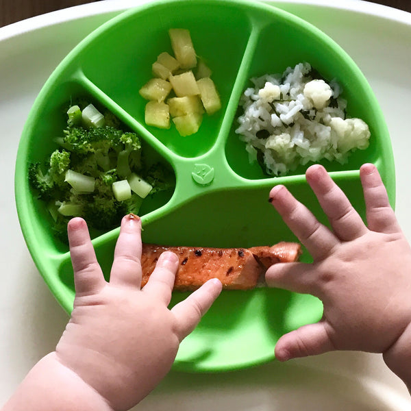Little baby hands poking at the food in the green Learning Plate made from Silicone