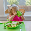 A little girl drinking out of the green Learning Cup made from Silicone and sitting with the rest of her green dinner wear