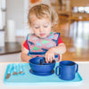 A two year-old boy reaching into the navy Learning Bowl made from Silicone