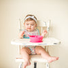A giggling toddler girl sitting in her high chair with the Pink Learning Spoon Set