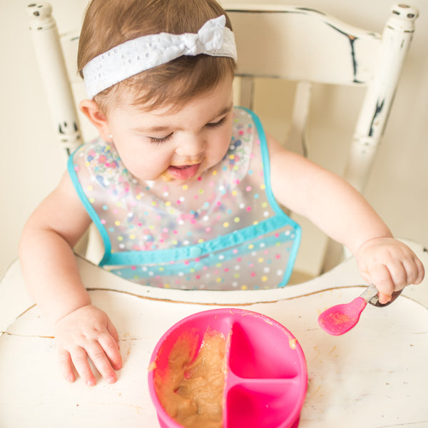 A little girl sitting in a white wooden high chair picking up her food with the Pink Learning Spoon Set