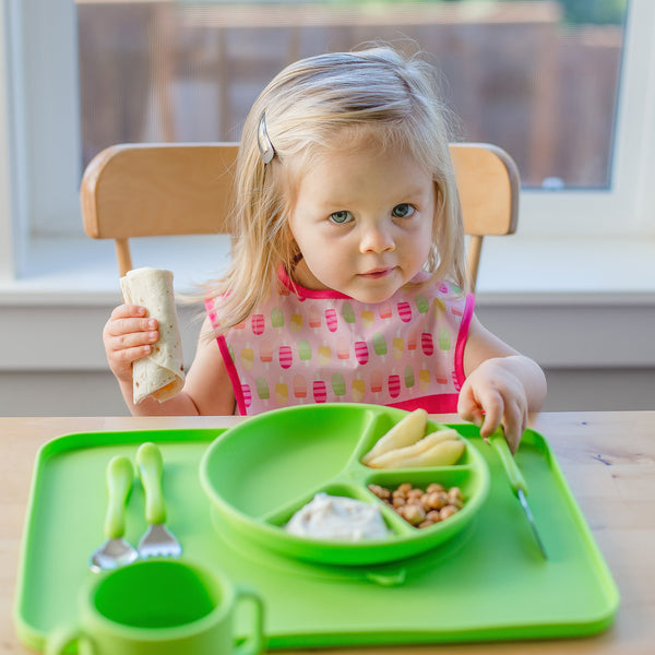 A young girl holding a burrito in one hand and the green Learning Cutlery Set in the other