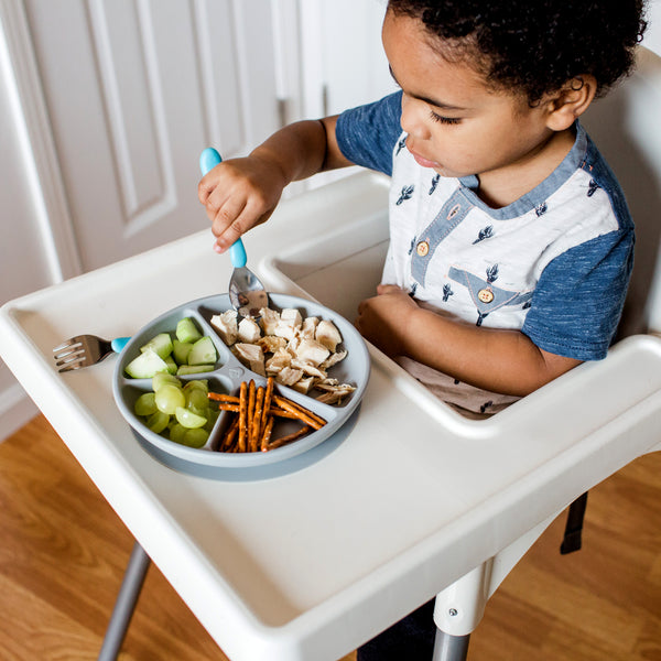 A young boy in a high chair using the aqua Learning Cutlery Set to eat his food