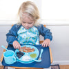 Young blonde toddler with a blue long sleeve bib and eat out of an Aqua Learning Plate made from Silicone