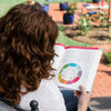 A woman reading the Grow Healthy. Grow Happy. The Whole Baby Guide in her backyard.
