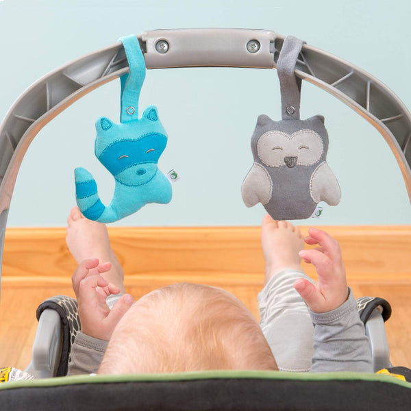 The blue raccoon and gray owl friends are attached to the handle of a carrier as a baby reaches up to play.