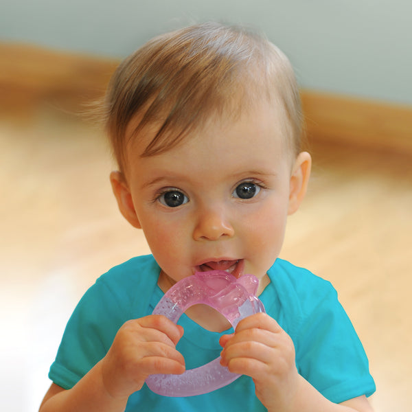 A wide-eyed 6 month old girl looking intently while gripping the light pink strawberry Cool Fruit Teether to her little mouth.
