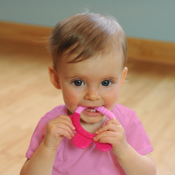 A wide-eyed 6 month old girl looking intently while gripping the pink Everyday Teether made from Silicone to her little mouth.