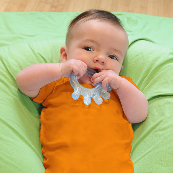 A little newborn boy laying on a green blanket and playing with the light blue cooling everyday teether in his mouth.