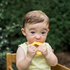 A little baby holding a yellow Cleaning Teether made from Silicone in her mouth.