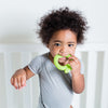 A cute little boy in a  white crib holding the green apple Fruit Teether made from Silicone in his mouth.