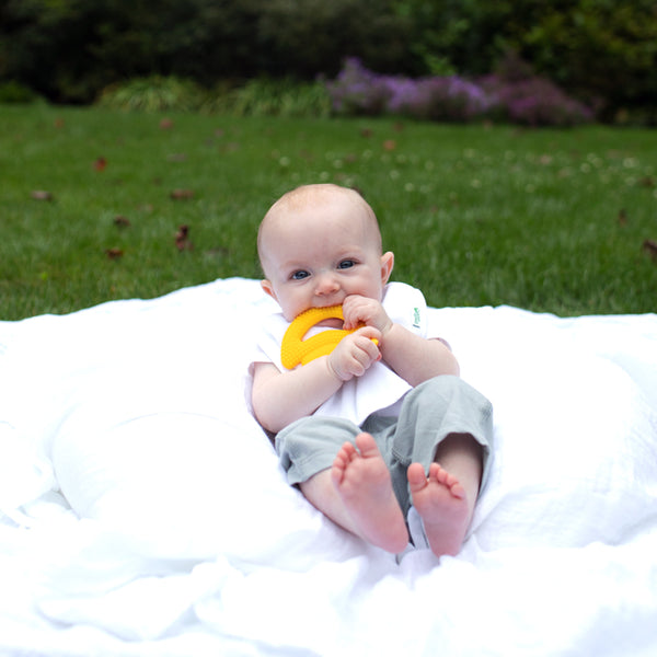 A little baby laying on a white blanket with the yellow banana Fruit Teether made from Silicone in his mouth