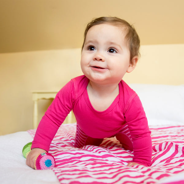 A girl toddler with a pink Long Sleeve Adjustable Bodysuit made from Organic Cotton on crawling across the bed