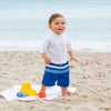 A young toddler about to walk off the towel onto the sand of a beach while wearing his Royal and Light Blue Color Block Trunks