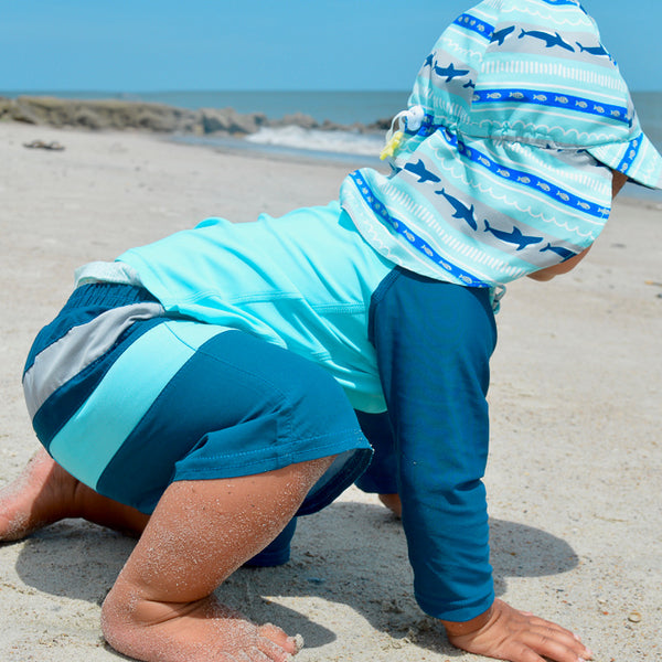 A young toddler boy about to stand up on the beach in his navy and aqua Color Block Trunks with Built-in Reusable Absorbent Swim Diaper