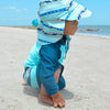 A young toddler boy kneeling and looking out on the beach in his navy and aqua Color Block Trunks with Built-in Reusable Absorbent Swim Diaper