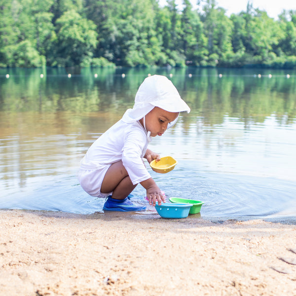 A toddle squatting on a beach to play with water boats in the lake while wearing an all white swim outfit along with a White Flap Sun Protection Hat.