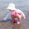 A young girl kneeling on the beach touching the water while wearing a white Breathable Swim and Sun Bucket Hat.
