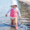 A young girl walking through the water on the beach while wearing a white Breathable Swim and Sun Bucket Hat.