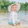A smiling baby girl sitting one a beach on a lake looking behind her at the viewer while wearing a white Brim Sun Protection Hat.
