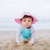 A little baby girl crawling on the beach towards the viewer while wearing a light pink Brim Sun Protection Hat.