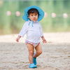 A little girl wearing a light blue Brim Sun Protection Hat while walking along the sand.