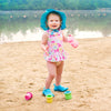 A rosy cheeked toddler standing on a beach lake wearing a ruffle swimsuit and a aqua Brim Sun Protection Hat.