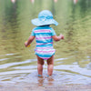 A toddler standing in the lake facing away while wearing a light blue Brim Sun Protection Hat.