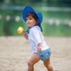 A young girl running with a yellow cup while wearing a royal blue Brim Sun Protection Hat.