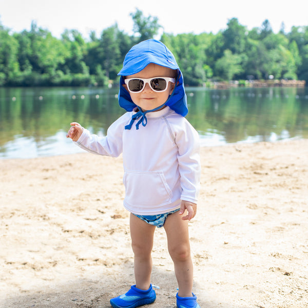 A little boy hanging out on a beach lake while wearing sunglasses and a Royal Blue Flap Sun Protection Hat.