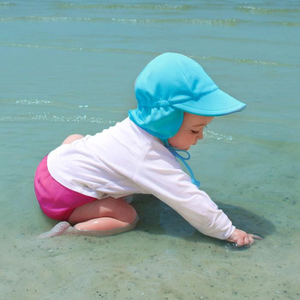 Little girl with an aqua Breathable Swim and Sun Flap Hat splashing in the water on the beach.