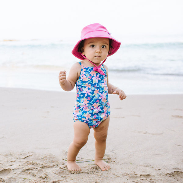 A young toddler girl trying to walk on the sand while wearing a hot pink Breathable Swim and Sun Bucket Hat.