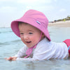 A smiling little girl laying on her belly in the shallow water on the beach while wearing an aqua Breathable Swim and Sun Bucket Hat.