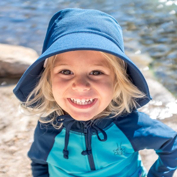 Young blonde boy smiling while wearing a navy Breathable Swim and Sun Bucket Hat by a river.