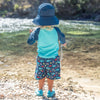 A little boy standing near the rocks in a river while wearing a navy Breathable Swim and Sun Bucket Hat.