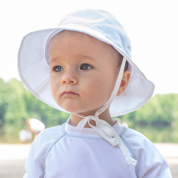 An up close view a toddler looking away from the camera with a white Bucket Sun Protection Hat on.