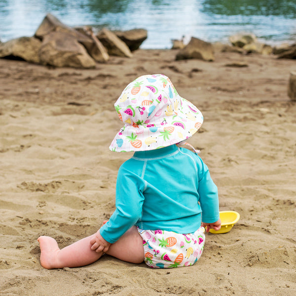 A little baby sitting on a beach lake facing away while wearing the white fruit Bucket Sun Protection Hat and matching swim diaper.