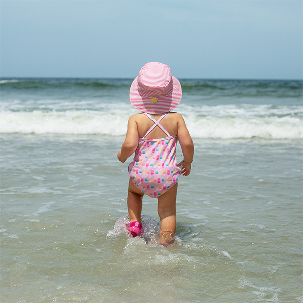 A young girl walking into the waves on the beach with a pink swim suit and the light pink pinstripe Bucket Sun Protection Hat.