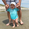 A smiling baby wearing the aqua Breathable Sun Protection Shirt while learning to walk and holding her parent's hand on the beach.